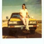 Just a Polaroid of some dude, sitting on a yellow car in the desert.